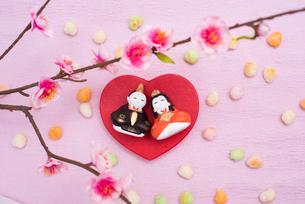 ハート型の台に乗った雛人形と桃の花,ひなあられの写真素材 [FYI01598452]