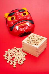 枡に入った煎り大豆と赤鬼のお面の写真素材 [FYI01598490]