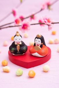ハート型の台に乗った雛人形と桃の花,ひなあられの写真素材 [FYI01598669]