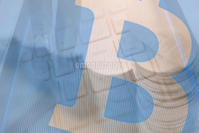 ビジネスマンの足元とキーボード,積み重ねた硬貨,ビットコインロゴマークの合成の写真素材 [FYI01598760]