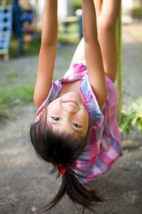 鉄棒で遊ぶ女の子の写真素材 [FYI01598762]