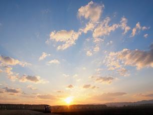 夕焼け雲とトラクターの写真素材 [FYI01598994]