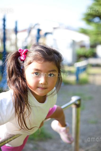 鉄棒で遊ぶ女の子の写真素材 [FYI01599176]