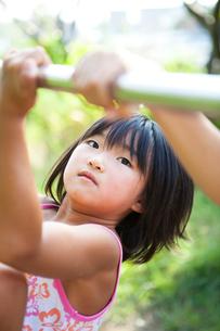 鉄棒で遊ぶ女の子の写真素材 [FYI01599479]