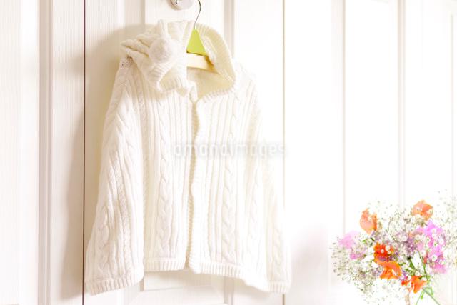 フックにかけたベビー服と花の写真素材 [FYI01599958]
