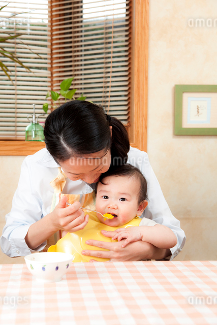 赤ちゃんに離乳食を食べさせる母親の写真素材 [FYI01600346]