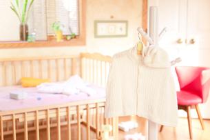 ベッドの前にあるハンガーにかけたベビー服の写真素材 [FYI01600405]