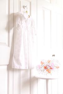 フックにかけたベビー服と花の写真素材 [FYI01600584]