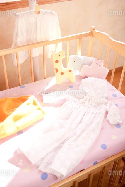 ハンガーとベッドにあるベビー服の写真素材 [FYI01600718]