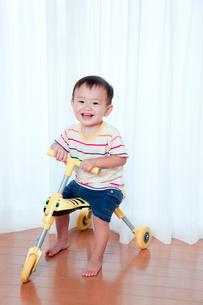 三輪車に乗って遊ぶ赤ちゃんの写真素材 [FYI01600756]