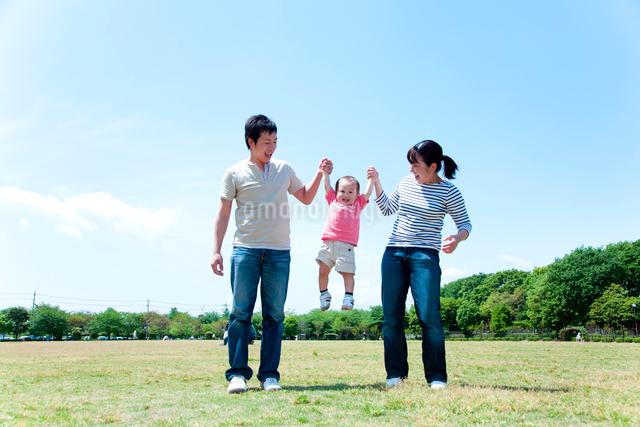 手を繋いで男の子を持ち上げる父と母の写真素材 [FYI01600805]