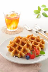 ブルーベリーとラズベリーとイチゴを添えたワッフルと紅茶の写真素材 [FYI01600806]