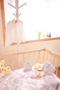 ハンガーとベッドにあるベビー服の写真素材 [FYI01600878]