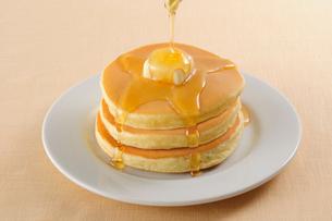 バターをのせてハチミツをかけたホットケーキの写真素材 [FYI01600985]