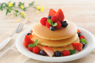 イチゴとブルーベリーとラズベリーをのせたホットケーキの写真素材 [FYI01601062]