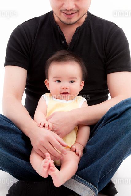 父親の組んだ脚に乗る赤ちゃんの写真素材 [FYI01601105]