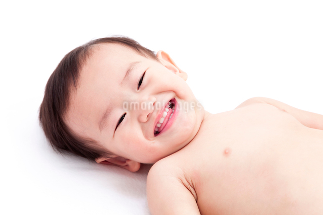 寝転んでほほえむ赤ちゃんの写真素材 [FYI01601154]