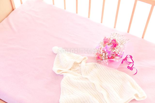 ベビーベッドの上のベビー服と花の写真素材 [FYI01601404]