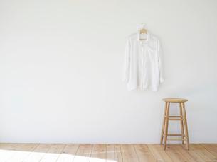 壁にかかった白いシャツとスツールの写真素材 [FYI01603475]