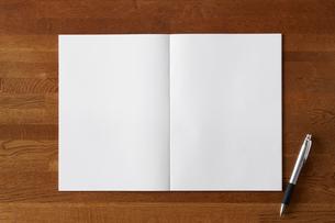 木の机と開いた白い無地のノートとペンの写真素材 [FYI01603534]
