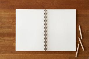 木の机と開いた白い無地のノートと色えんぴつの写真素材 [FYI01603556]