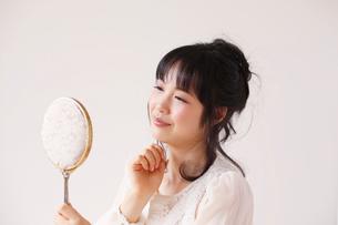 鏡を見る笑顔の女性の写真素材 [FYI01603665]