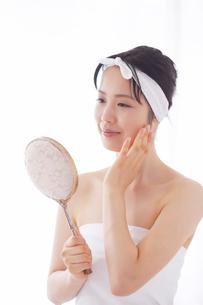 鏡をみてほほえむスキンケアをする女性の写真素材 [FYI01603714]