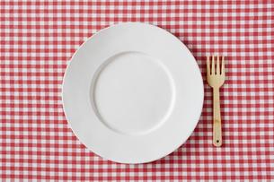 赤いチェックの布と白い皿とフォークの写真素材 [FYI01603734]