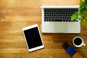 テーブルに置かれたノートパソコンとタブレットPCとコーヒーの写真素材 [FYI01603868]