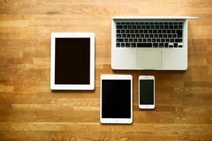 テーブルに置かれたノートパソコンとタブレットPCとスマートフォンの写真素材 [FYI01604061]
