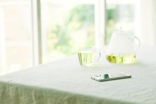 テーブルに置かれたティーポットとカップとスマートフォンの写真素材 [FYI01604136]
