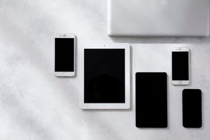 白とグレーで塗装された背景とタブレットPCとスマートフォンとノートパソコンの写真素材 [FYI01604173]