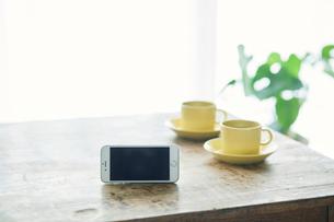 コーヒーカップとテーブルとカーテンとスマートフォンの写真素材 [FYI01604233]