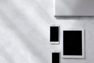 白とグレーで塗装された背景とタブレットPCとスマートフォンとノートパソコンの写真素材 [FYI01604259]