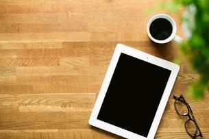 テーブルに置かれたコーヒーとタブレットPCの写真素材 [FYI01604324]
