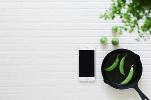 キッチンに置かれた白いタイルと野菜と観葉植物とスマートフォンとスキレットの写真素材 [FYI01604366]