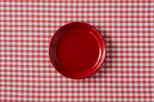 赤いチェックの布と赤い皿の写真素材 [FYI01604388]
