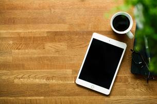 テーブルに置かれたコーヒーとタブレットPCの写真素材 [FYI01604409]