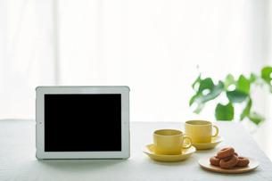 コーヒーカップとテーブルとカーテンとタブレットPCの写真素材 [FYI01604412]