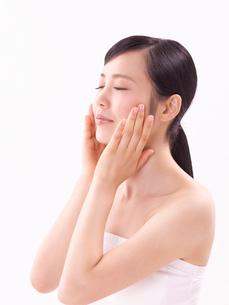 頬に手をそえスキンケアをする女性の写真素材 [FYI01604418]