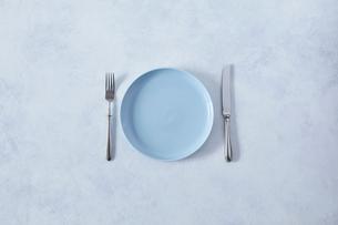 白とグレーで塗装された背景と水色の皿とカトラリーの写真素材 [FYI01604419]