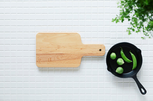 キッチンに置かれた白いタイルとカッティングボードとスキレットの写真素材 [FYI01604483]