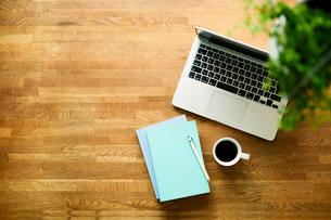 テーブルに置かれたノートパソコンとコーヒーの写真素材 [FYI01604488]