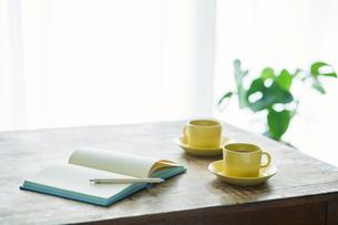 コーヒーカップとテーブルとカーテンとノートとペンの写真素材 [FYI01604517]