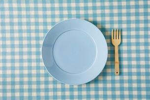 水色のチェックの布のテーブルクロスと水色の皿とフォークの写真素材 [FYI01604535]