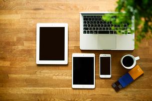 テーブルに置かれたノートパソコンとタブレットPCとスマートフォンの写真素材 [FYI01604691]