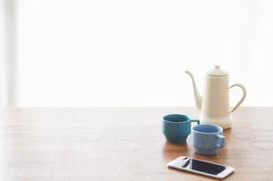 木のテーブルとスマートフォンとコーヒーの写真素材 [FYI01604694]