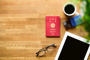 テーブルに置かれたパスポートとコーヒーとタブレットPCの写真素材 [FYI01604710]