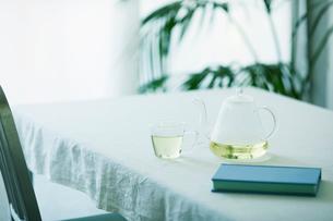 テーブルに置かれたティーポットとカップと観葉植物と本の写真素材 [FYI01604724]