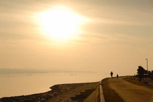 宍道湖湖畔を走る親子と夕日の写真素材 [FYI01604731]